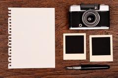 Cuaderno en blanco con la pluma, los marcos de la foto y la cámara Imagen de archivo libre de regalías
