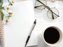 Cuaderno en blanco con la pluma y vidrios al lado de una taza de café fotos de archivo