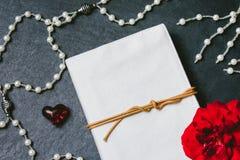 Cuaderno en blanco con las huevas y corazón rojo en fondo de piedra negro Imágenes de archivo libres de regalías