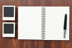 Cuaderno en blanco con los marcos de la pluma y de la foto Imagen de archivo libre de regalías