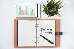 Cuaderno en blanco con palabra de la ESTRATEGIA EMPRESARIAL y tableta digital con la carta de negocio en la endecha blanca del pl fotos de archivo libres de regalías