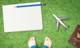 Cuaderno en blanco en hierba con la materia del transporte aéreo Imagen de archivo