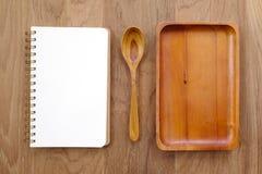 Cuaderno en blanco, placa de madera y cuchara en la tabla Imagen de archivo