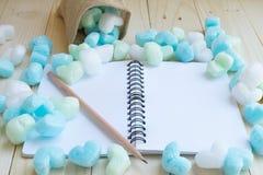 Cuaderno en blanco rodeado con los corazones y el lápiz verdes y azules Fotos de archivo