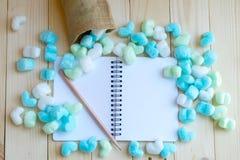 Cuaderno en blanco rodeado con los corazones y el lápiz verdes y azules Fotografía de archivo