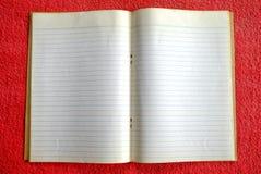 Cuaderno en blanco viejo en la estera roja Foto de archivo libre de regalías