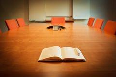 Cuaderno en el escritorio de la sala de reunión Foto de archivo libre de regalías