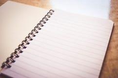 Cuaderno en la tabla de madera Fotos de archivo