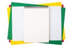 Cuaderno en las hojas del papel coloreado Fotos de archivo libres de regalías
