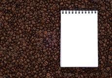 Cuaderno en los granos de café del fondo Imagen de archivo libre de regalías