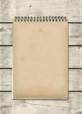 Cuaderno espiral cerrado en una tabla de madera blanca Imágenes de archivo libres de regalías