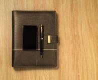 Cuaderno espiral con un móvil y una pluma en el fondo del escritorio Fotografía de archivo
