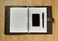 Cuaderno espiral con un móvil y una pluma en el fondo del escritorio Imagen de archivo libre de regalías