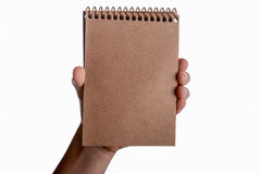 Cuaderno espiral en mano del niño Fotos de archivo