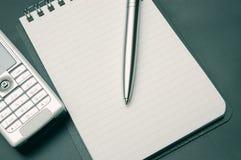 Cuaderno espiral, pluma y teléfonos en fondo gris oscuro Imagenes de archivo
