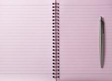 Cuaderno espiral rosado y una pluma Fotografía de archivo libre de regalías
