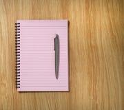 Cuaderno espiral rosado y una pluma en el fondo del escritorio Foto de archivo libre de regalías