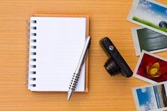 Cuaderno, foto, pluma y cámara. En el suelo o Imágenes de archivo libres de regalías