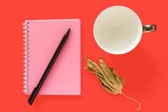 Cuaderno, hoja seca, taza y una pluma fotos de archivo libres de regalías