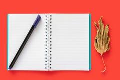 Cuaderno, hoja seca y una pluma fotografía de archivo