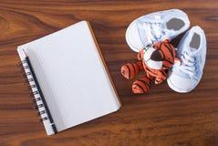 Cuaderno, juguete y zapatos de bebé fotografía de archivo libre de regalías
