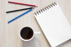 Cuaderno, lápices y taza de café en la tabla fotografía de archivo