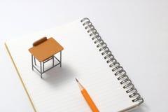 Cuaderno, lápiz y escritorio miniatura Fotografía de archivo libre de regalías