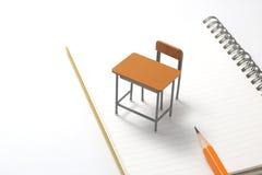 Cuaderno, lápiz y escritorio miniatura Imágenes de archivo libres de regalías