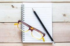 Cuaderno, lápiz y lentes en la tabla de madera Imagen de archivo libre de regalías