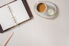 Cuaderno limpio, taza de caf? y macaron colorido en la visi?n de escritorio gris Endecha acogedora del plano de la moda del desay imagen de archivo