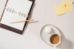 Cuaderno limpio, taza de caf? y macaron colorido en la visi?n de escritorio gris Endecha acogedora del plano de la moda del desay imágenes de archivo libres de regalías