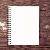 cuaderno llano blanco para el poste de comercialización de los medios sociales con el fondo de madera foto de archivo