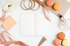 Cuaderno, macoroons, accesorios, botella de perfume y flor en blanco Fotos de archivo libres de regalías