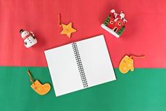 Cuaderno, muñeco de nieve, Papá Noel y la Navidad o decoración y ornamento del Año Nuevo en fondo rojo y verde Fotos de archivo
