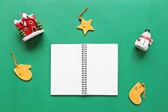 Cuaderno, muñeco de nieve, Papá Noel y la Navidad o decoración y ornamento del Año Nuevo en fondo verde Foto de archivo