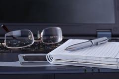 Cuaderno negro con la mentira de la pluma y de los vidrios de la libreta Fotos de archivo libres de regalías