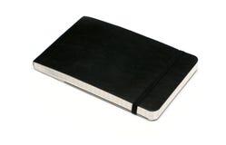 Cuaderno negro en el fondo blanco Imágenes de archivo libres de regalías