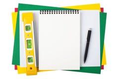 Cuaderno, nivel y una pluma negra en el papel coloreado Foto de archivo