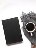Cuaderno o libro con café sólo caliente en el escritorio blanco bufanda gris en el fondo Visión superior Endecha plana Fotos de archivo