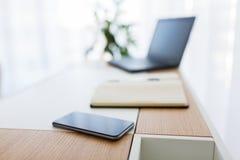 Cuaderno, ordenador portátil y smartphone en la tabla de la oficina Imagenes de archivo