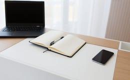 Cuaderno, ordenador portátil y smartphone en la tabla de la oficina Fotografía de archivo libre de regalías