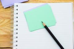 Cuaderno, papel de nota y lápiz negro Imágenes de archivo libres de regalías