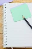 Cuaderno, papel de nota y lápiz negro Imagen de archivo libre de regalías