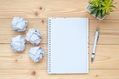 cuaderno, papel desmenuzado, pluma y en la tabla Comienzo del Año Nuevo, creativo, idea, resolución, solución, estrategia y misió fotos de archivo