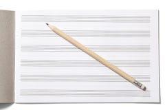 Cuaderno para las notas musicales y el lápiz Imagen de archivo