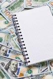 Cuaderno para las notas que mienten en fondo del dinero fotografía de archivo
