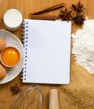 Cuaderno para las recetas con los ingredientes de la hornada Fotos de archivo libres de regalías