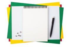 Cuaderno, pernos del empuje y una pluma negra en el papel coloreado Imágenes de archivo libres de regalías