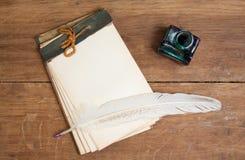 Cuaderno, pluma de la tinta de la canilla e inkwell viejos en el Ba de madera imagen de archivo libre de regalías