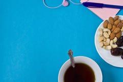 Cuaderno, pluma, flores, platillo con las frutas secadas en un fondo azul, el lugar de trabajo de las mujeres foto de archivo